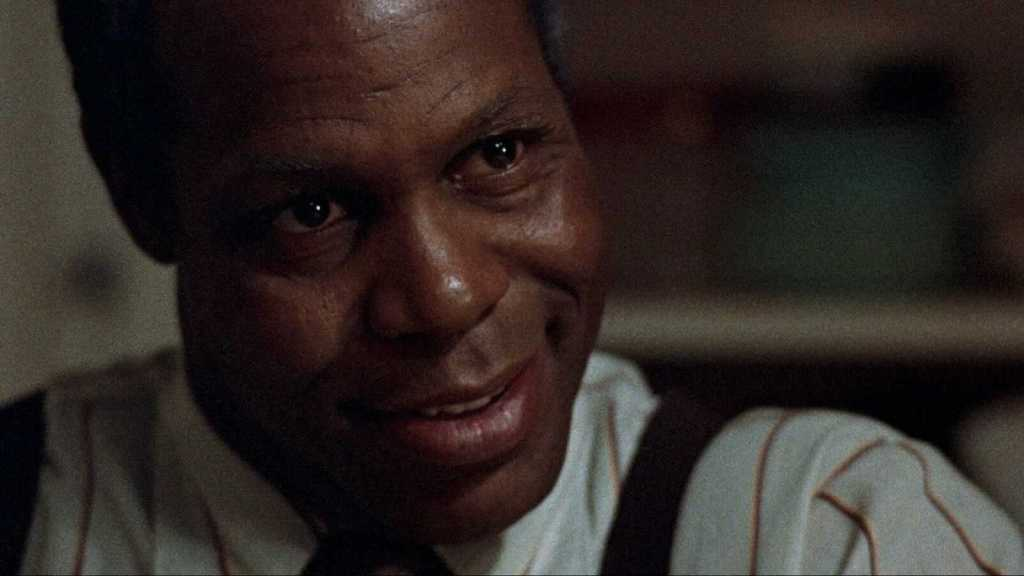 A Black man in close-up, who has an unsettling expression on his face. He wears suspenders and a white striped shirt.