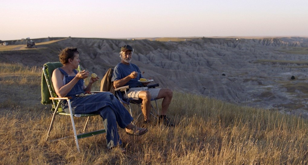 On the edge of a cliff, an older man and woman sit on deckchairs and eat a meal together. The landscape around them is highlighted in shadows and golden sun.