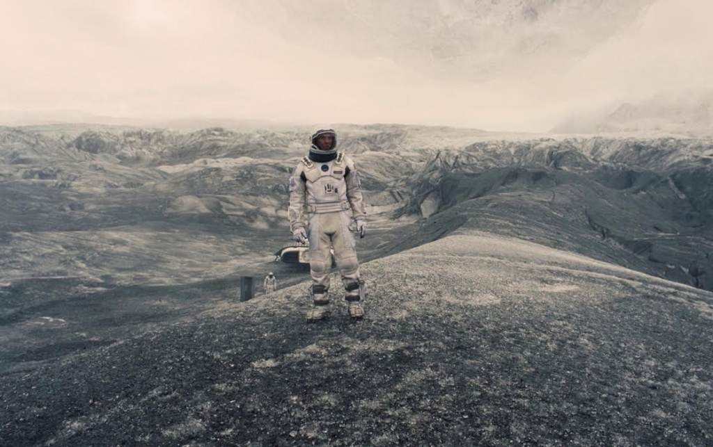 An astronaut stands in the center of a desolate landscape, with craters and an ashen grey sky.