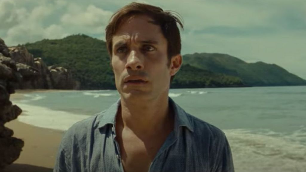 A middle-aged man with short dark hair on a beach, seen from the chest up and wearing a blue collared shirt. He has a concerned look on his face.