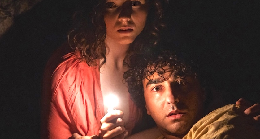 A young man and a young woman in a dark cave. They are huddled together seeming worried while the girl holds a light.