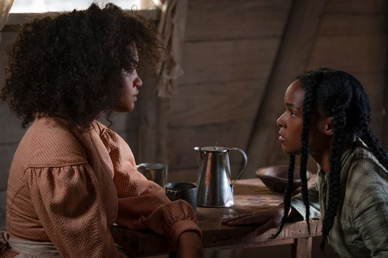 Two Black women sitting at a table and looking at one another. The woman on the left has an afro and wears a long-sleeved top, while the woman on the right has braids and wears a plaid shirt. A metal pitcher is seen on the wooden table between them.