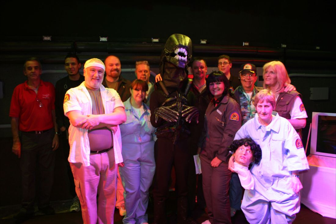 A group of middle-aged people, many of whom are dressed in costume as characters from the film 'Alien'. The actor playing the Alien stands in the centre, surrounded by others in spacesuits. A woman on the far right holds a severed head prop.