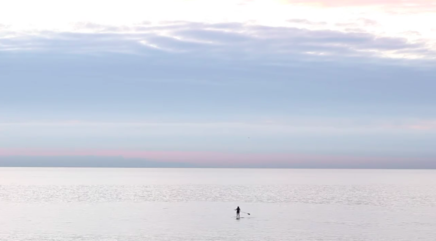 Marie (Jane Adams) way out on the ocean, standing on her board and paddling away from the camera alone. It's a wide static shot, perfectly framing the meeting of the ocean and sky horizontally. It feels never-ending. Colours of pink, orange, light and darker blue.
