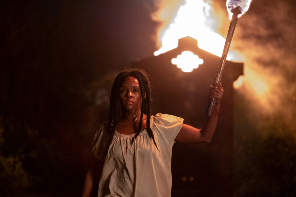 With a sullen look on her face, Veronica holds a burning torch walking away from a shed behind her that is lit on fire.