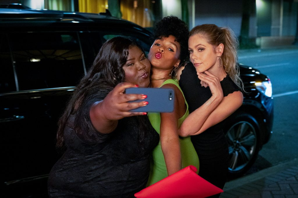Veronica poses with two friends, played by Gabourey Sidibe and Lily Cowles, for a selfie in front of a black SUV.  She wears a green dress, while they are in black.