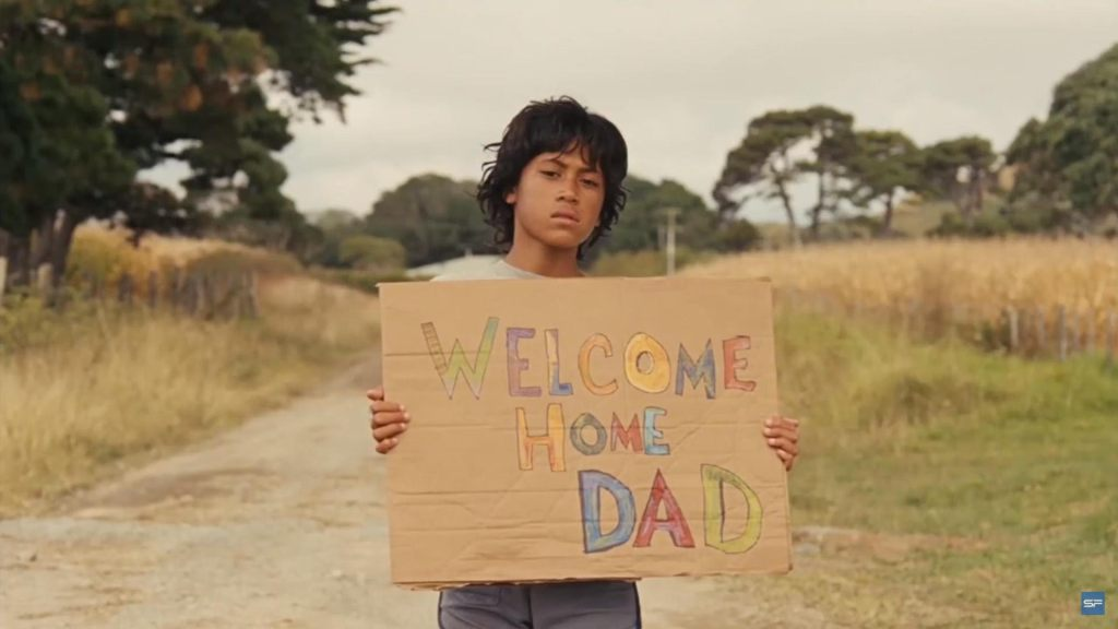 """A young boy with dark hair holding up a cardboard sign that reads """"welcome home dad"""" in crayon letters. He stands in the middle of the road, with grassland behind him."""