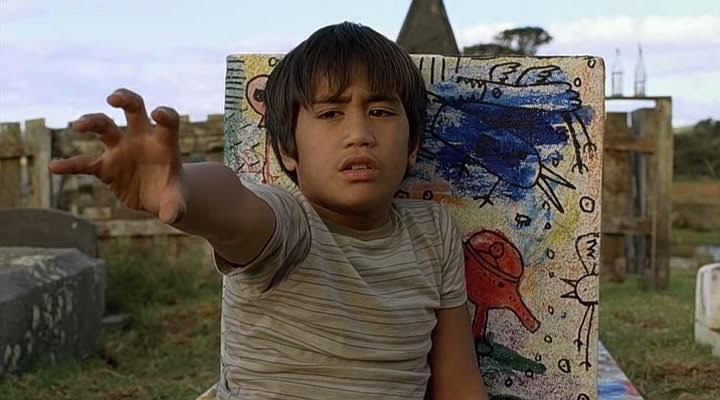 A young boy wearing a striped shirt reaches out. There is a colourful painting visible behind him, with a bird in blue and another figure in red.