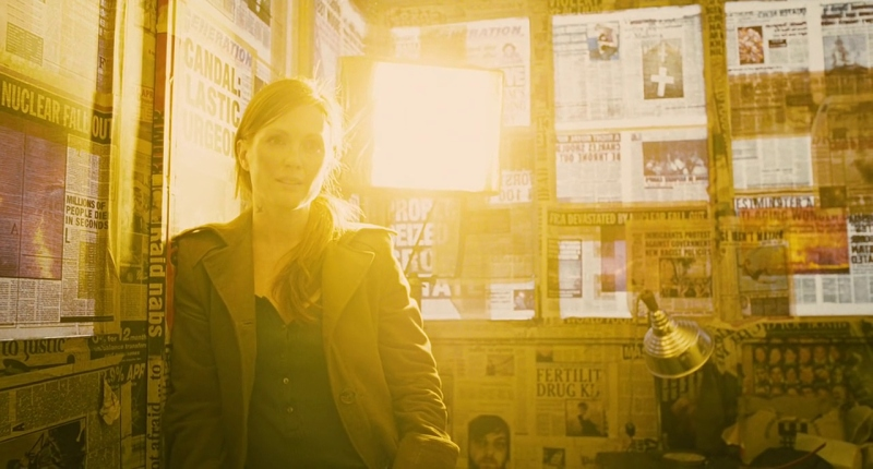Julianne Moore as Julian in Children of Men stands in front of a newspapered window. A yellow lamp illuminates her from behind.