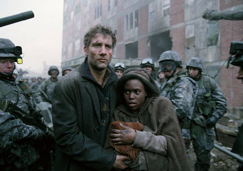 Clive Owen as Theo and Clare-Hope Ashitey as Kee in Children of Men make their way through a crowd of soldiers. Theo is bloodied and Kee holds her blanketed newborn.