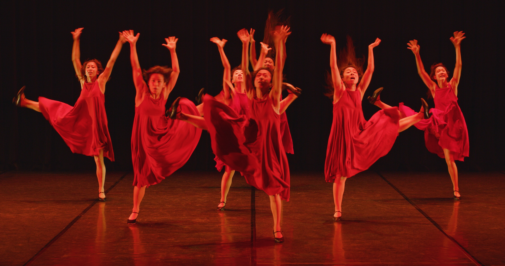 Japanese women dancing on stage wearing red dresses. They have their arms raised upwards, and one leg extended out.