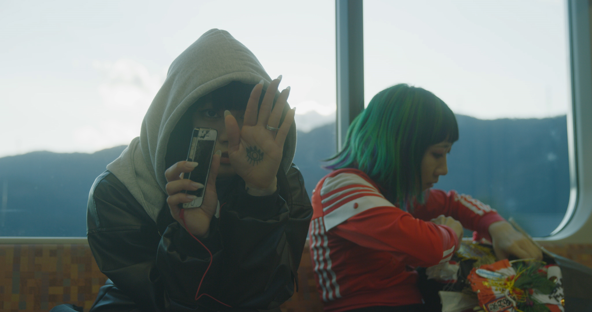 A Japanese girl wearing a hoodie and holding a hand in front of her face while sitting on a train. An eye in ink is visible on her palm, which she holds in front of her right eye. Another girl sits beside her, with a red jacket and blue-green hair, who is working on a costume.