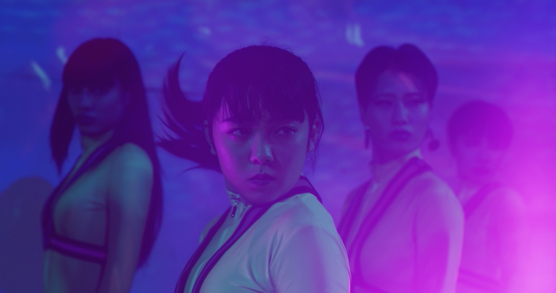 Several Japanese girls performing a dance. Yume is in focus in the middle, with her brunette hair tied up and worn in bangs. The others are out of focus but they wear the same white top.