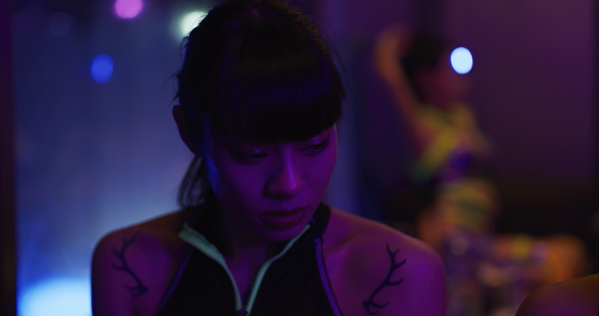 A young Japanese girl looks to the side. Her dark hair is worn in bangs and she has on a top with neon green down the front. She wears