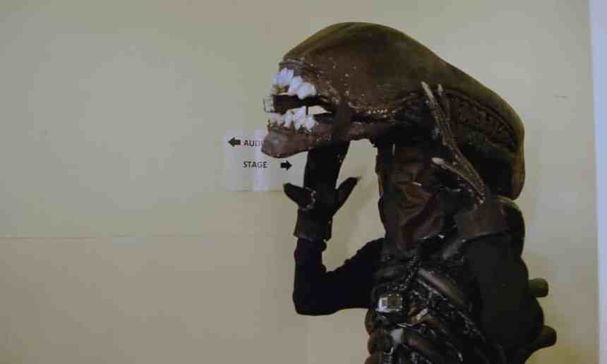 An actor dressed in costume as the Alien holds up his headpiece. The elongated black contraption covers his face and features a row of white teeth. The rest of the outfit consists of black gloves and a black top and chest piece.