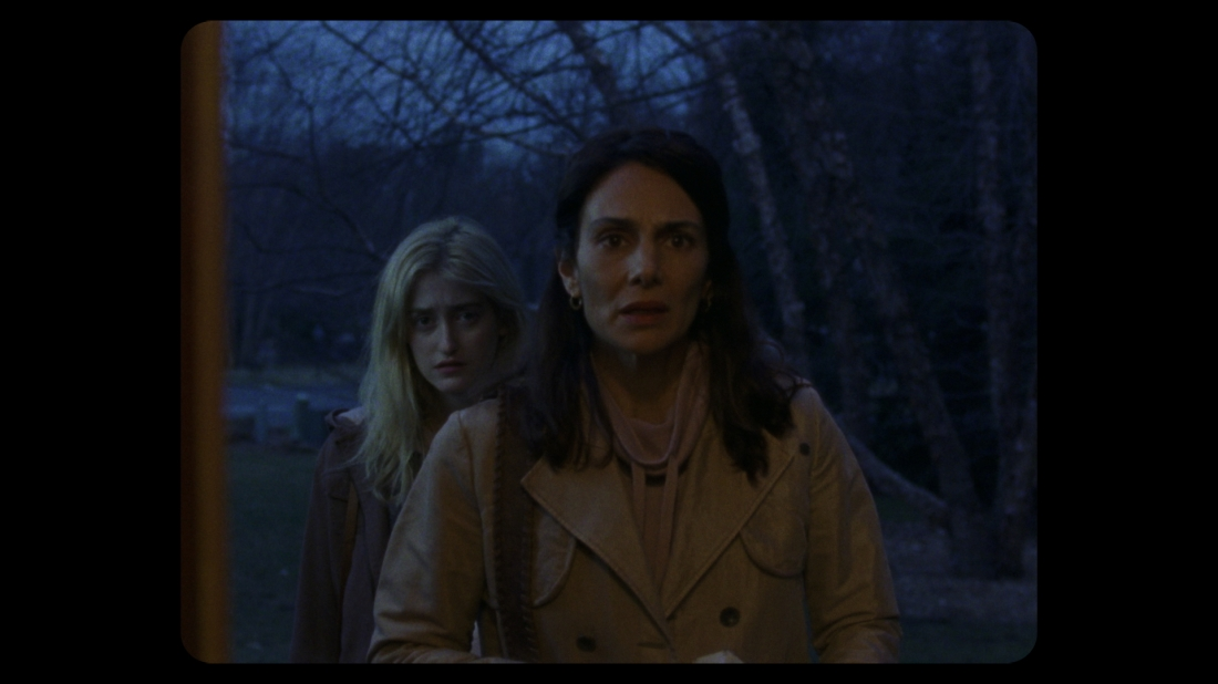 A brunette middle aged woman wearing a tan coat looks on in surprise. A younger blonde woman stands behind her, and the two are framed in the doorway. It is night, with trees visible behind them.