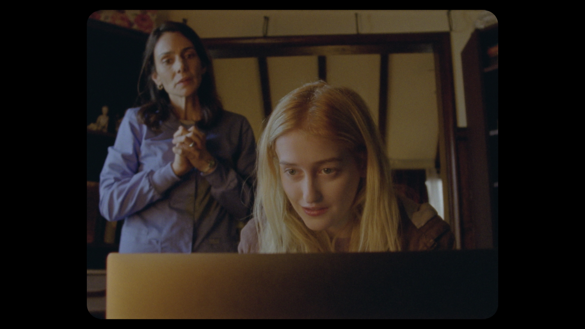 A young blonde woman sits behind a computer, smiling. An older brunette woman stands behind her, wearing a blue shirt. They are in an office space.