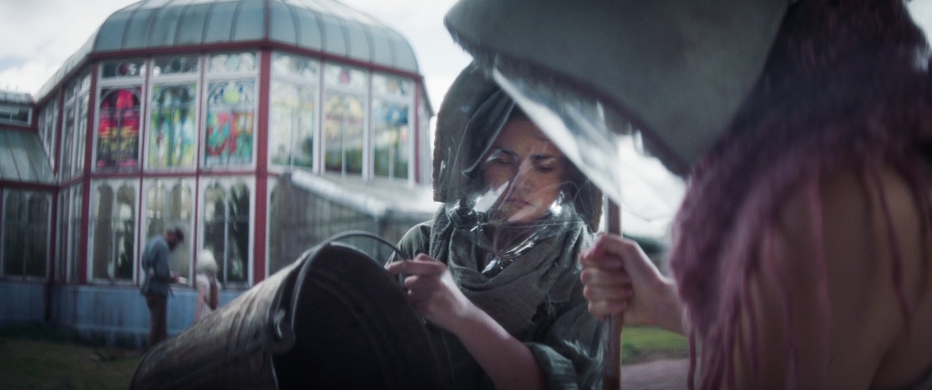 A young woman wearing a protective facial mask and loose clothing while holding a pail. A greenhouse with stained glass windows is out of focus behind her. Another person stands to her right wearing the same protective gear.