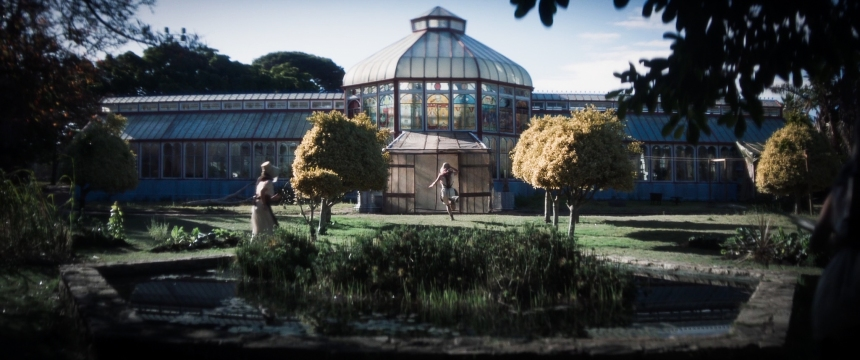 A greenhouse with stained glass windows visible from afar. Two figures can be seen from afar— one running in front of the building and the other outside. It is daytime, and they are surrounded by green foliage.