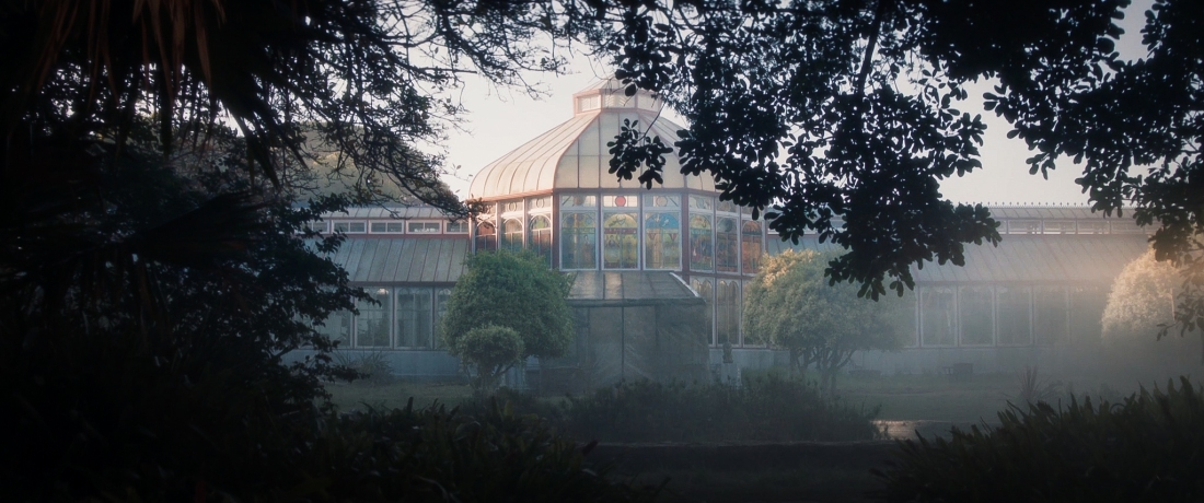 A picturesque greenhouse with stained-glass windows seen from afar. It is surrounded by trees, and there is a mist.