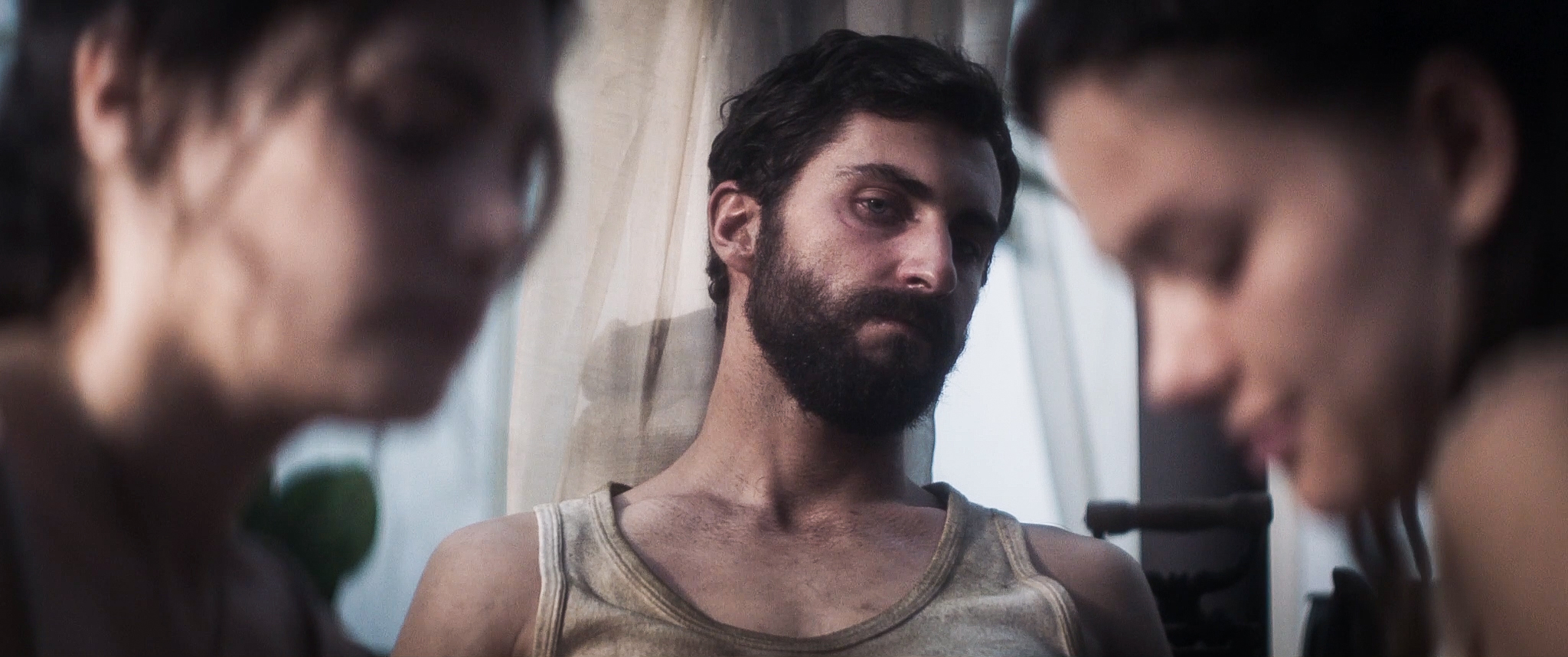 A bearded man with dark hair and a dirty tank top. He is visible from the chest up and between two young women in out of focus close up.