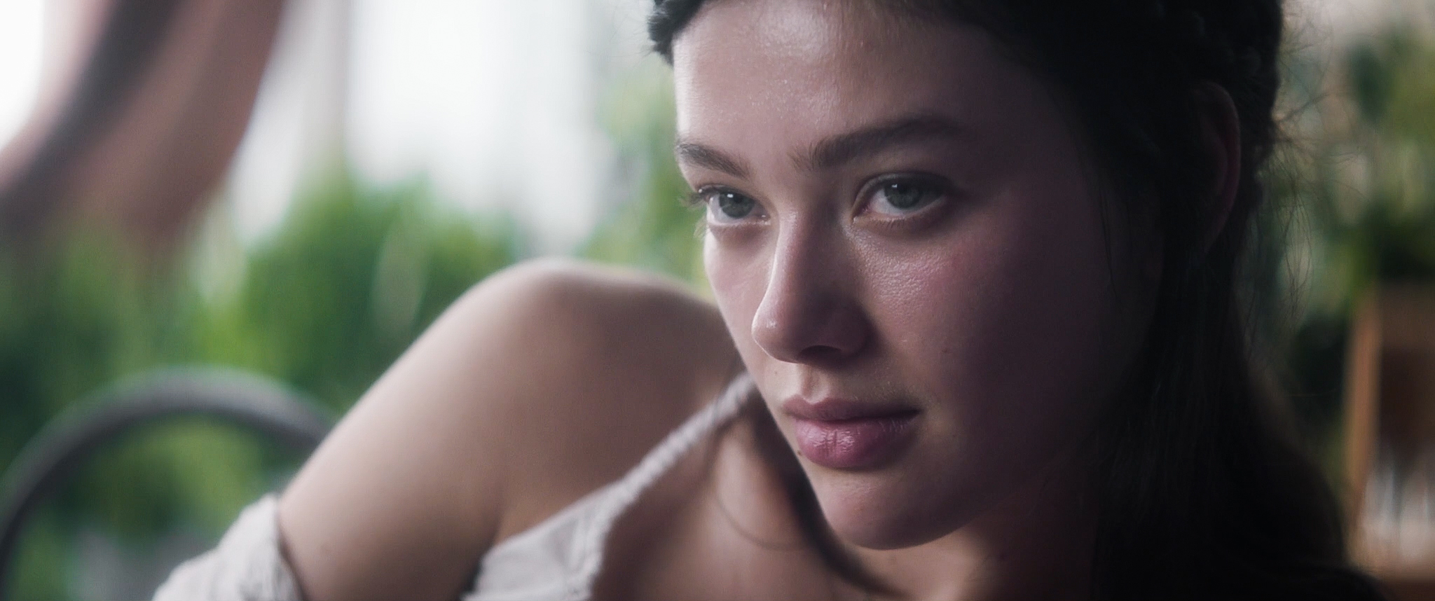 A young brunette woman seen from the shoulders up. Greenery is out of focus behind her, and she gazes at something off-screen.
