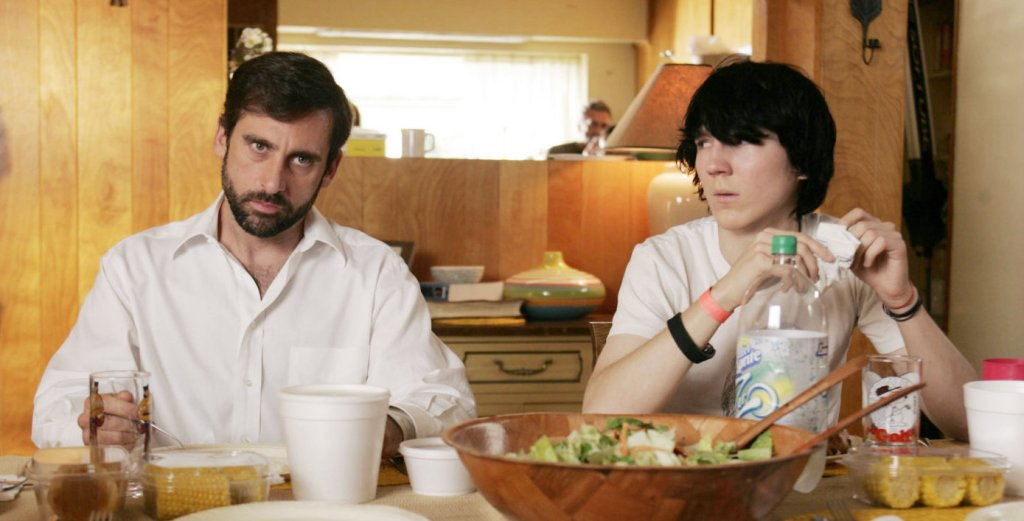 Two men wearing white sitting at a kitchen table. The older man wears a collared white shirt and appears unamused, while the younger man wears a t-shirt and has short, emo-style hair while looking over at him. A bowl of salad and corn on the cob can be seen in front of them.