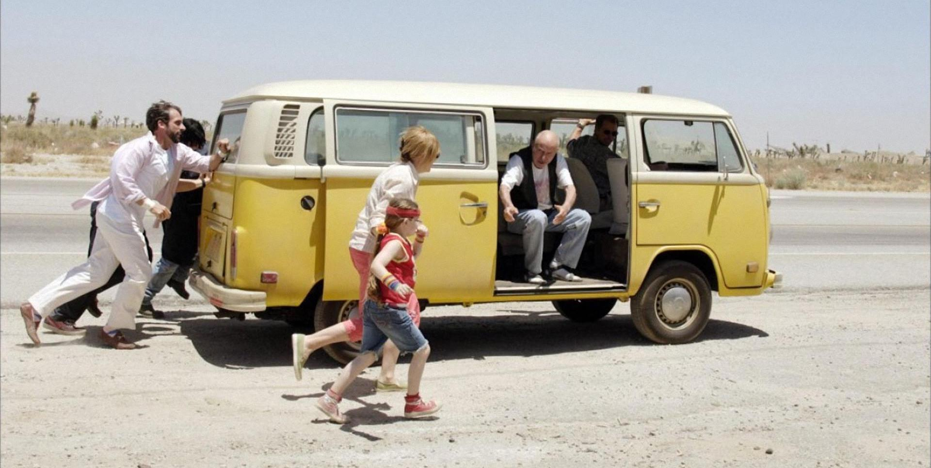 A yellow van with its doors open on a stretch of road. Two men are seen inside, while a woman and a young girl run beside it. The girl is wearing a bright red top and jean shorts, while the woman wears a white jacket and pink jeans. Two men run behind the van— one wearing white and one wearing black— helping to push it.