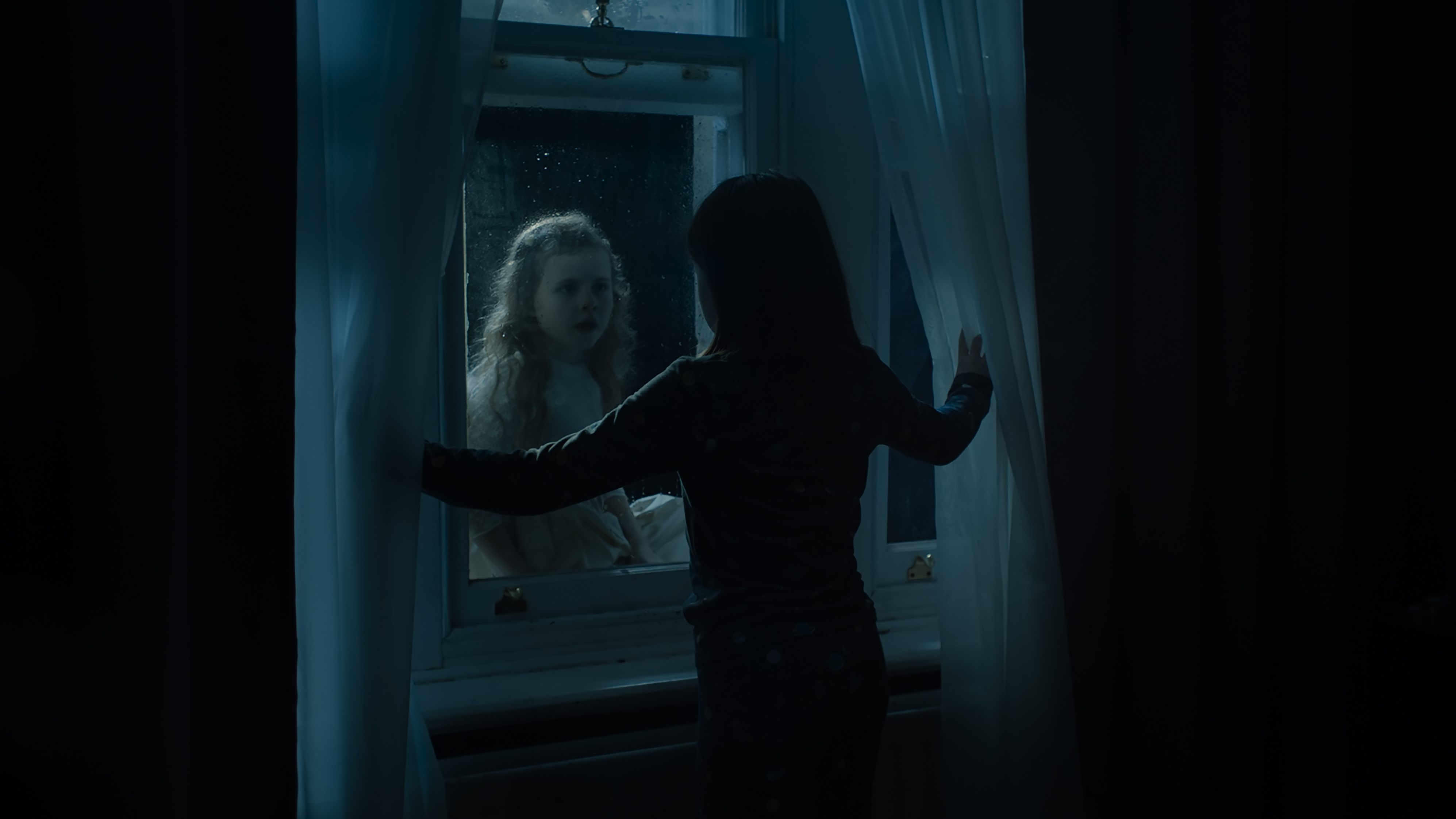 A young girl seen from behind in shadow standing in front of a closed window. A young girl with light hair and a white dress can be seen on the other side of the glass.