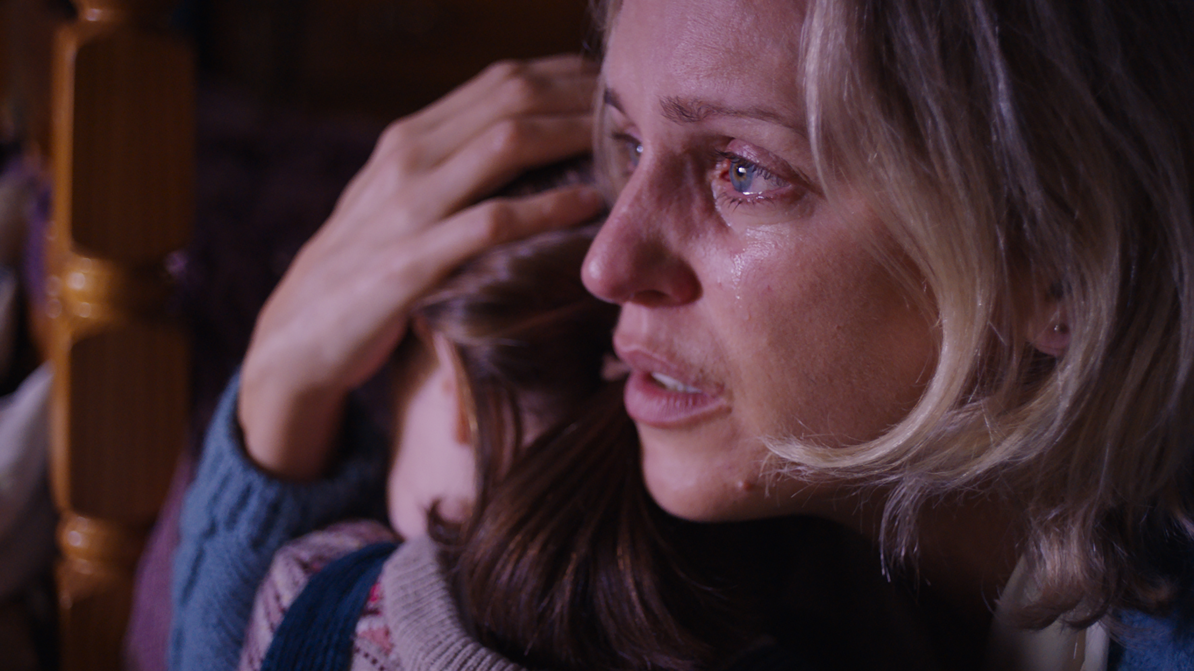 A blonde woman crying in close-up. She holds a young brunette girl close, with a protective