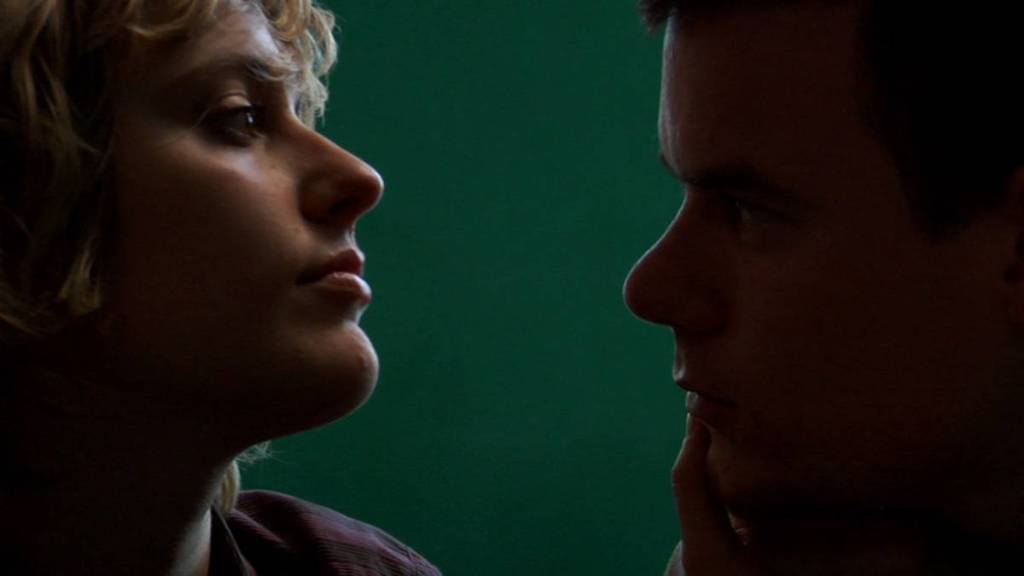 Close-up of James (Swanberg) and Mattie (Gerwig), Mattie to the frame's left and James to the right. It's a dark shot, with shadows darkening James' face, while light hits the highpoints of Mattie's face lighting up her chin, lips, cheekbones and nose. Mattie's head is lightly tilted upwards, in a stern position, as if she's the one in control in the frame. While looking at him, she holds James' face in her hand. James, with a more concerned facial expression, looks into her eyes.