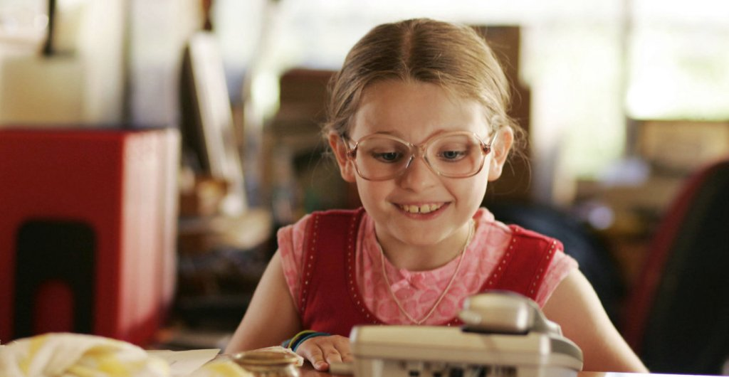 A young girl wearing a pink top and big glasses. Her hair is pulled back and she has a big toothy smile as she looks down at the object in front of her.