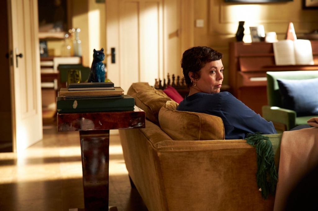 Anne, portrayed by Olivia Colman, sitting on the couch in the living room.