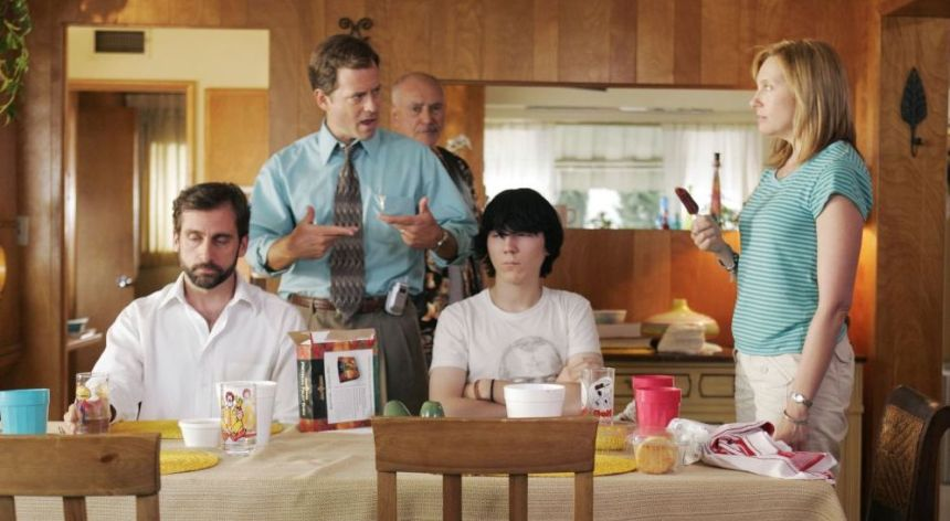 Two men in white shirts sitting at a kitchen table that has been set. The older man has a beard and neutral expression, while the younger man has dark emo-style hair and crossed arms. A man in a blue shirt stands between them angrily gesturing to a woman, who is wearing a blue striped shirt. An older man is also visible behind them.