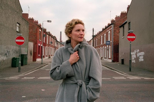 Courtesy of: Sally Potter/Sony Pictures Alt text: A woman stands centre frame, with a work-class street stretching out behind her. She is clutching her grey woollen coat around her and her face is unflinching.