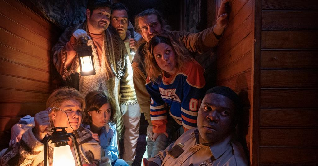 Finn sits against the corner of a wall, with the rest of the core cast of characters anxiously awaiting something that's around the corner