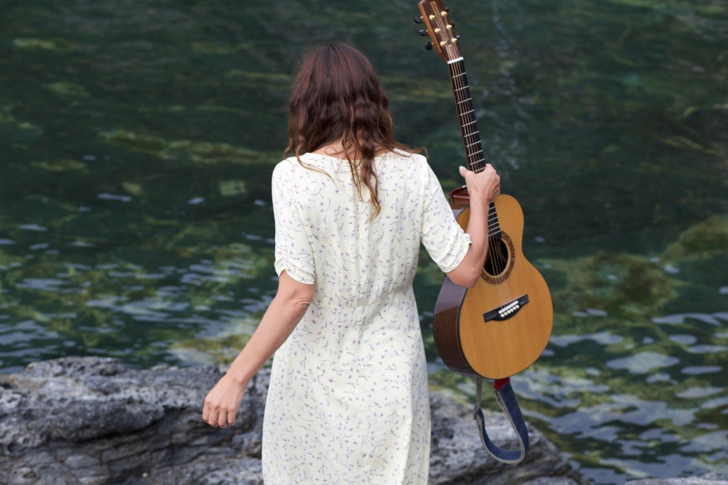 A woman with dark brown hair facing away from the camera. She holds an acoustic guitar in her right hand while facing the sea.