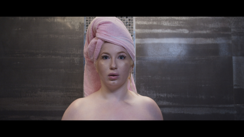 Kasia Szarek looks directly into the camera with a startled expression. She wears a pink towel on her head.