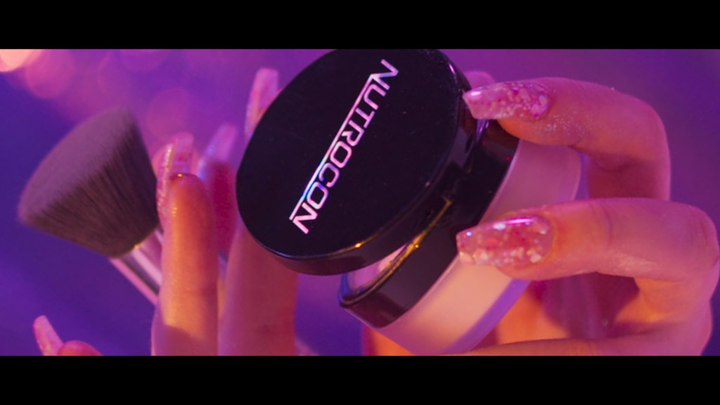 A pink manicaured hand holds a Nutrocon makeup container and an applicator brush.