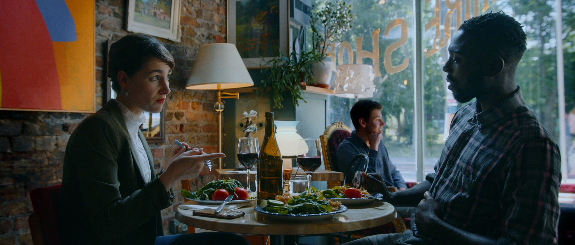 A young brunette Caucasian woman sits across the table at a restaurant from a Black man. She appears unimpressed, while his mouth is open. There is a table of food in front of them, as well as a brick wall with art and a window behind them with part of the writing . A man sits near the window.