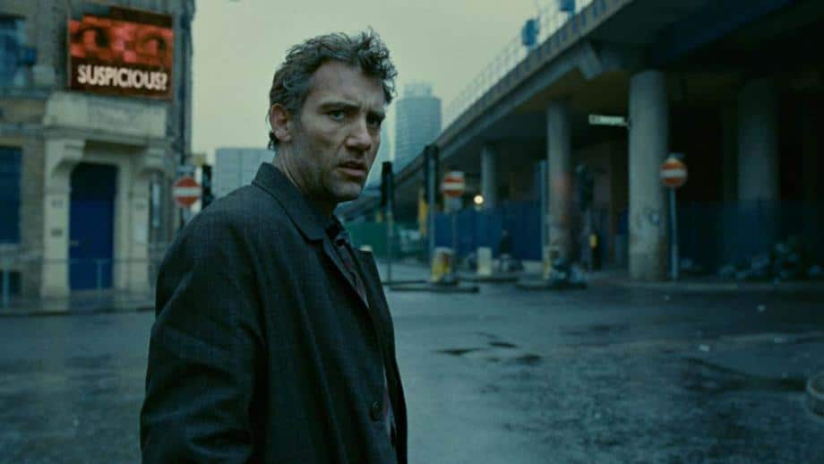 The protagonist of Children of Men, Theo, looks sombre in a dismally grey future London. A motorway bridge sits in the background as does a propaganda sign with the word 'Suspicious?' indicating the mood of the film