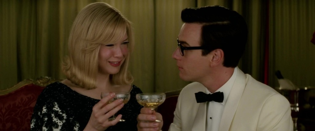 A man and a woman having drinks while sitting on a couch. They look at each other with drinks in their hands. The woman wears a dress and smiles, while the man wears a white tuxedo and has an unreadable expression.