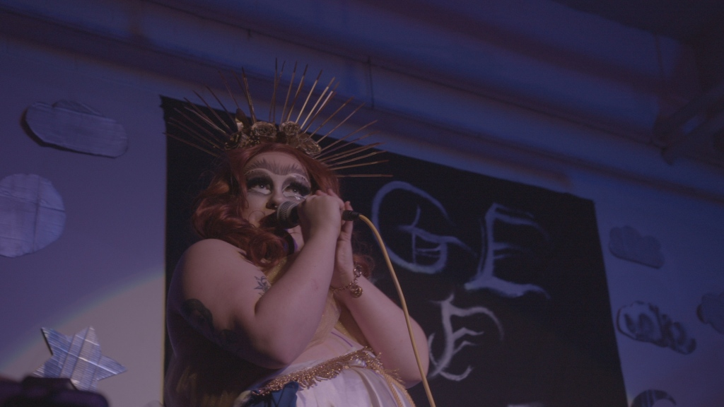 A drag queen stands on stage, holding a microphone up. She has a unibrow, mid-length red curls, and a spiky golden head accessory. Part of a banner can be seen behind her, along with cut-out shapes on the wall.