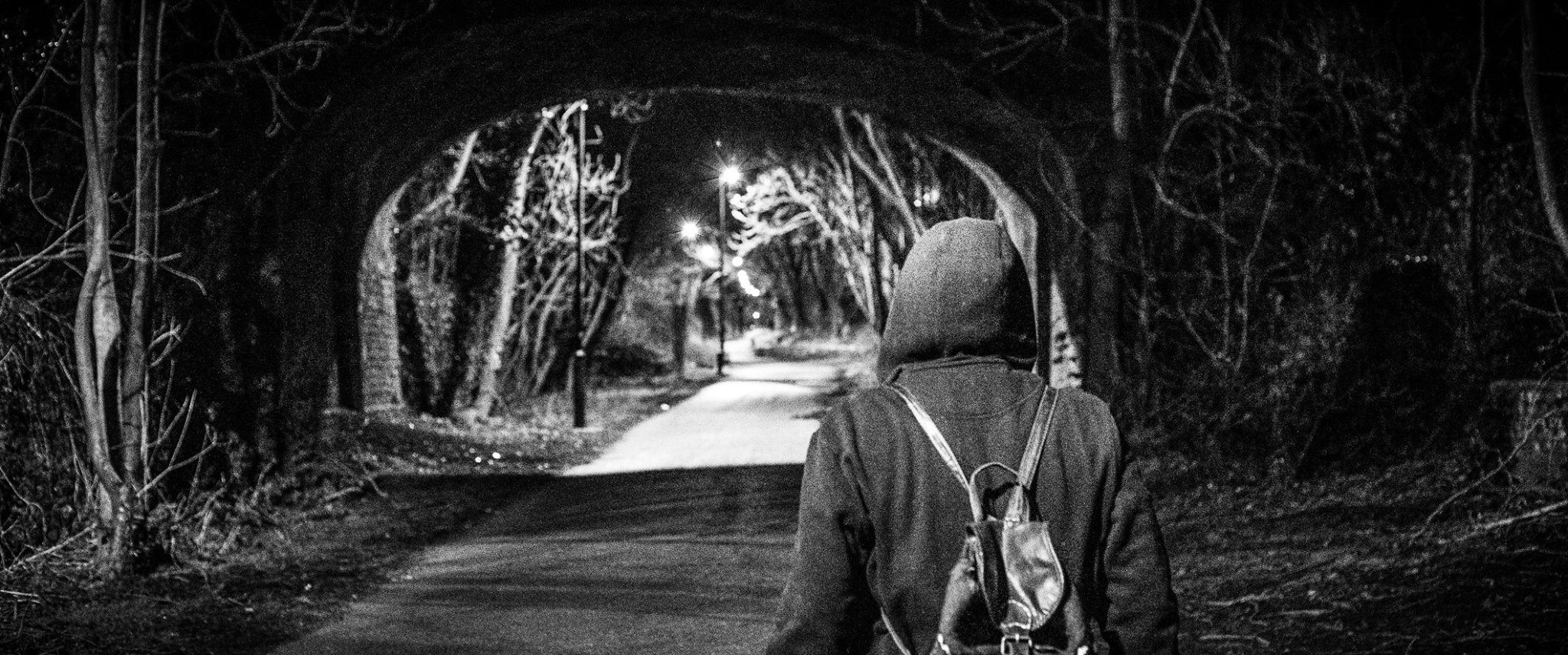 A black-and-white still of a woman shown from behind. She wears a hoodie and carries a backpack, while walking towards a tunnel. L