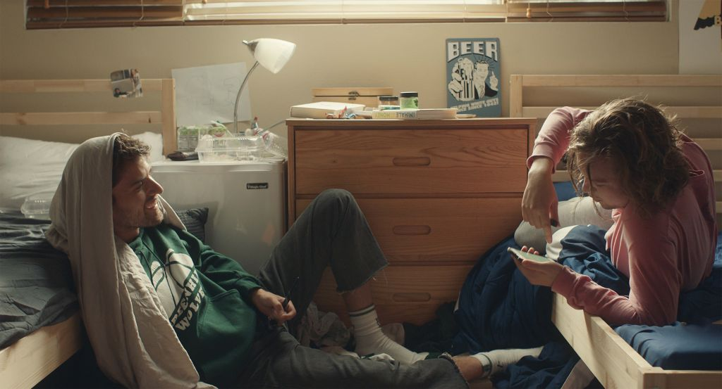 Two young men in a college dorm room. One has short brunette hair and wears a green hoodie with another hoodie draped over his head, leaning against a bed. The other has messy brunette hair and facial hair, wearing a light pink long sleeve shirt. He looks down, pointing to something on his phone.
