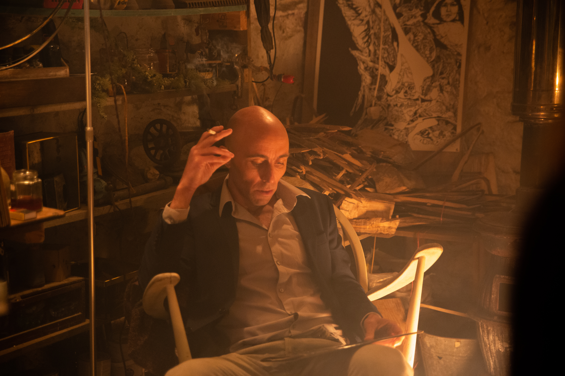A bald man wearing a collared shirt and suit jacket while sitting in a chair. His left hand is raised to his head and he looks deeply in thought, with a workshop full of odd objects as his backdrop.