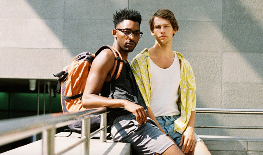 Harry and Johannes lean against a railing and look into the camera pensively.