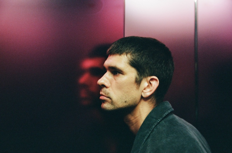 A man stands in front of a pink-lit wall. He is visible in profile view, with his face reflecting on the metal.