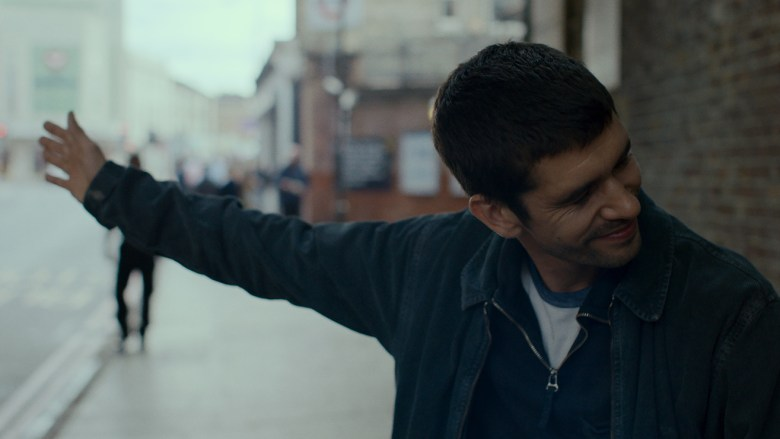 A man stands on the street wearing casual clothes. He is smiling, with his head turned to the right, and his left arm is outstretched. Buildings and people are out of focus behind him.