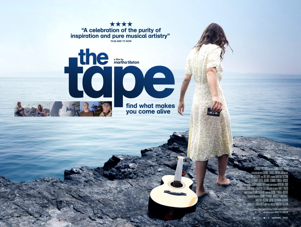 """A poster for the film 'The Tape'. A woman faces away from the camera wearing a long floral dress with short sleeves and holding a cassette tape out. A guitar rests on the rocks behind her, and she faces the sea. A four-star review of the film is featured, as well as the film's title in big bold letters with stills from the film underneath. The poster also includes the tagline and the tagline """"find what makes you come alive"""""""